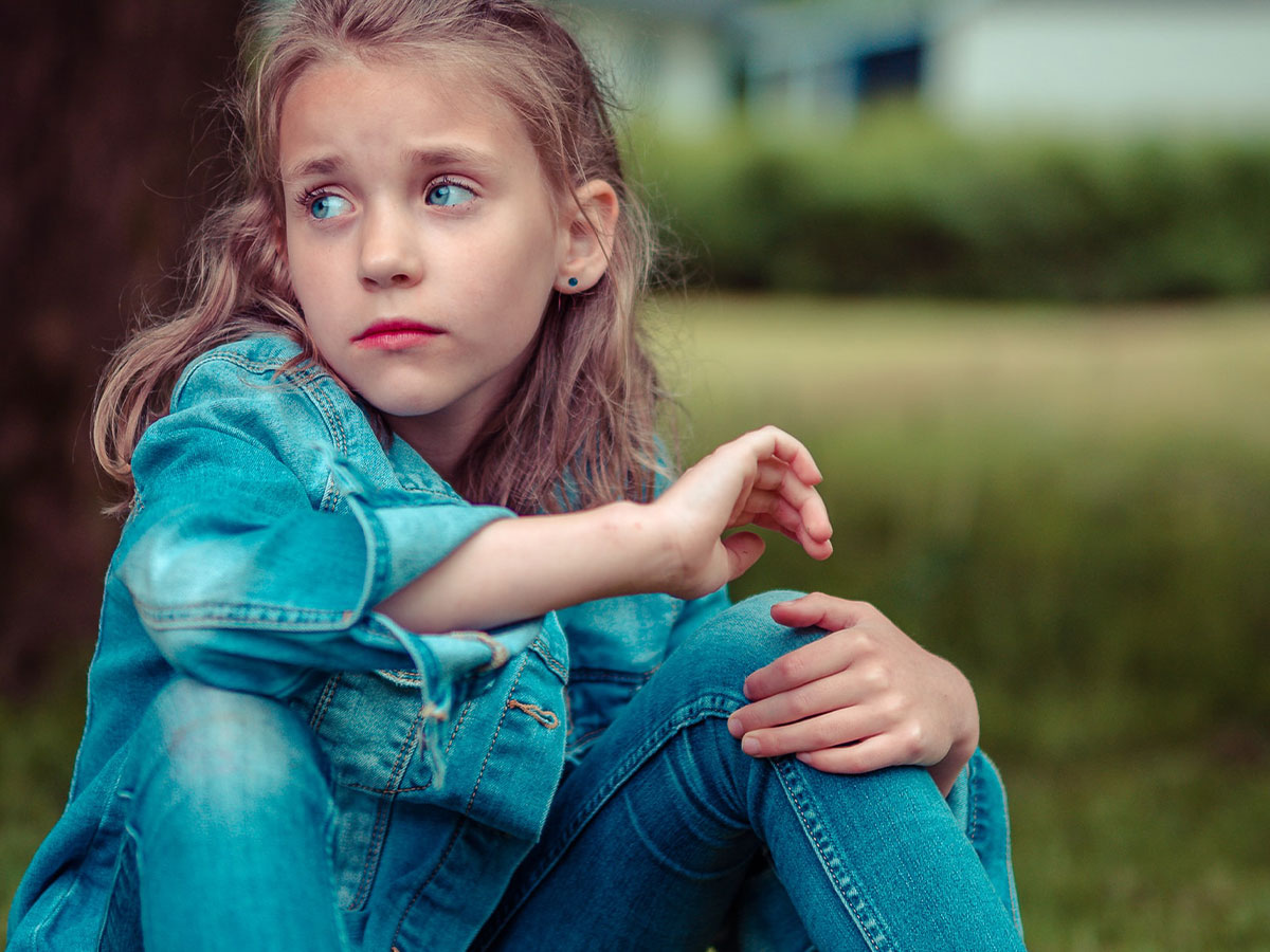 A young girl wearing jeans sitting in the grass