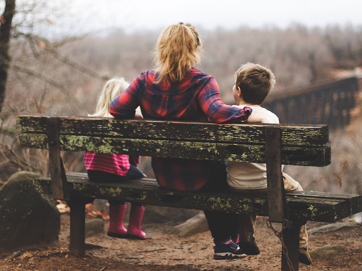 Woman sitting on a bench with two kids looking at a bridge