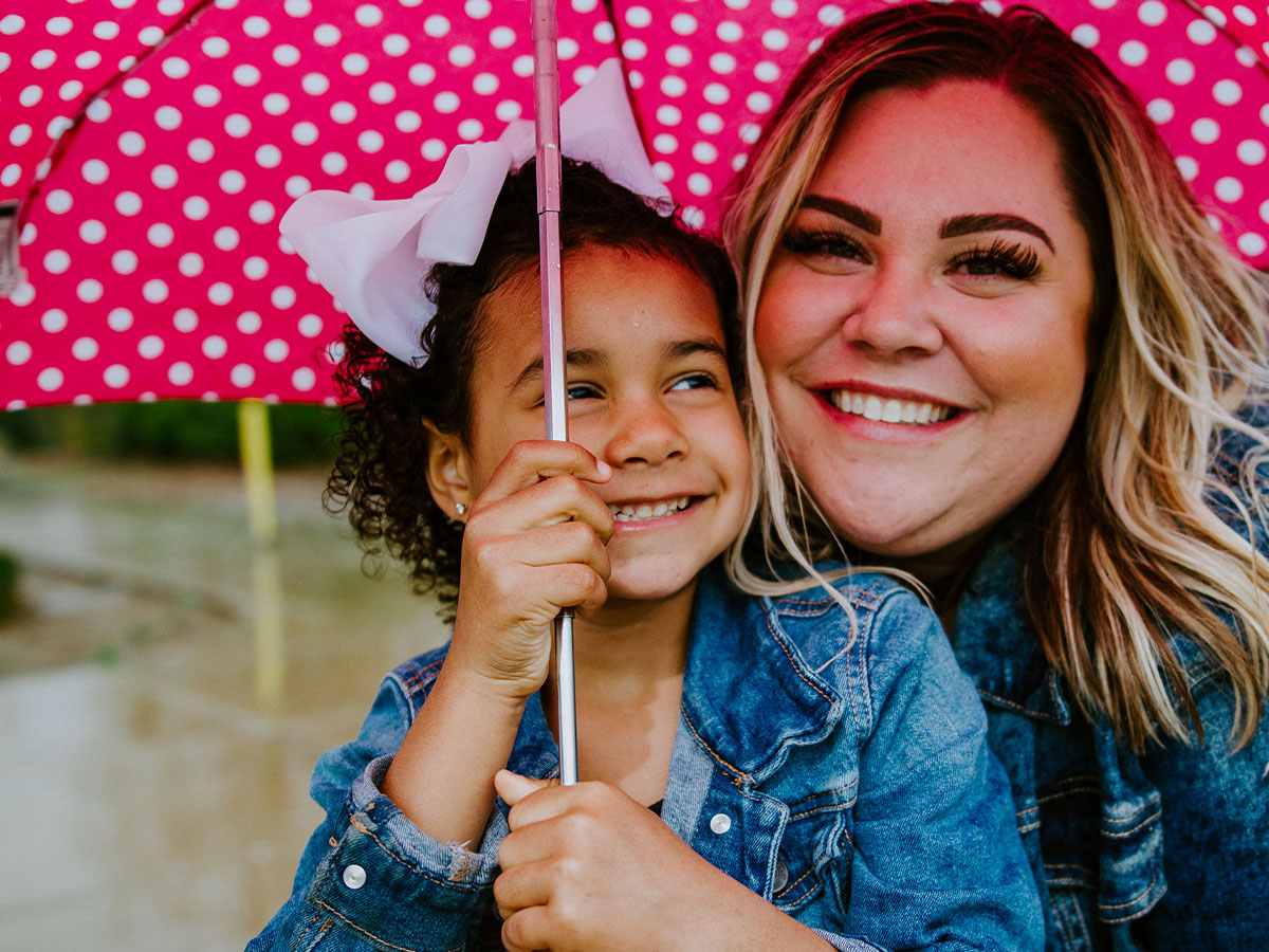 A woman and young girl in jean jackets huddled under an umbrella