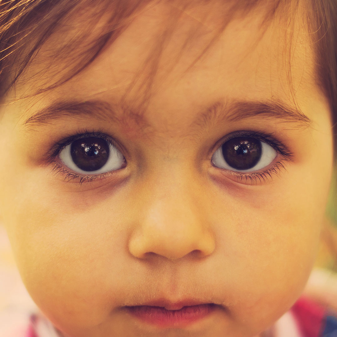 Young child with sad eyes looking at the camera.
